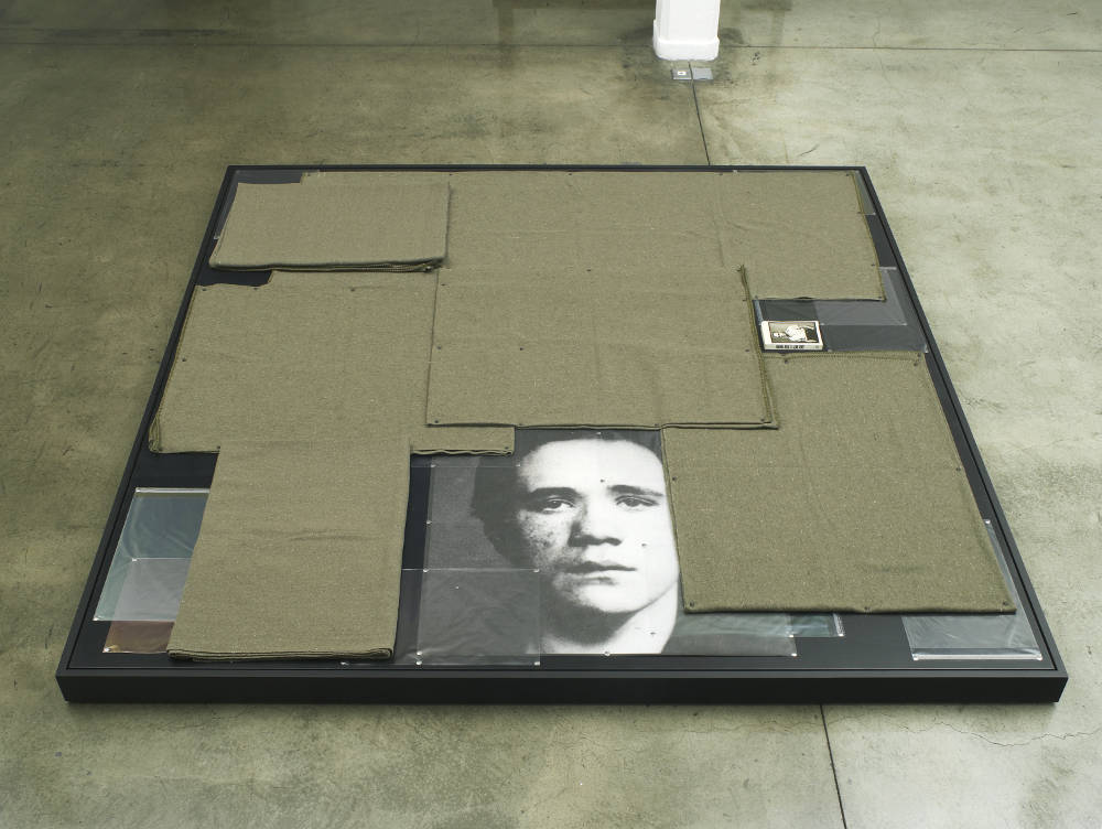 Tom Burr, Sexual Soft Target, 2017. Green military style blankets, black upholstery tacks, direct to surface print, clear plastic photographic sleeves, steel push pins, paperback copy of 'Funeral Rites' by Jean Genet' (1948), powder coated aluminium, painted plywood 9 x 240 x 240 cm