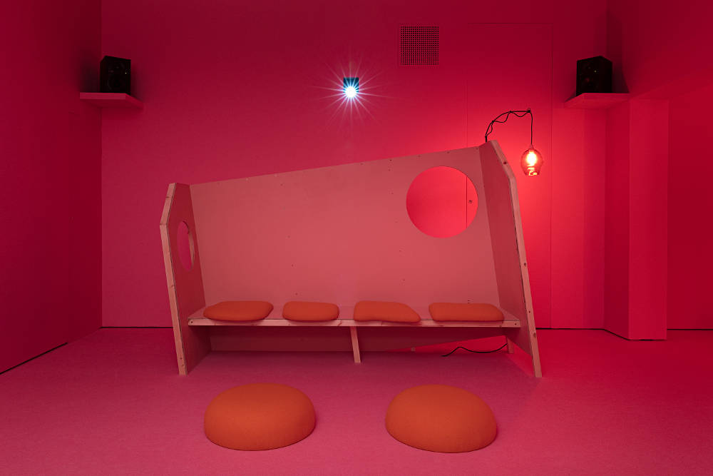 Anne Hardy, Area of Overlap (installation), 2018. Mixed media (digital projection, custom-made bench, upholstered seating and light) dimensions variable © Anne Hardy, courtesy Maureen Paley, London