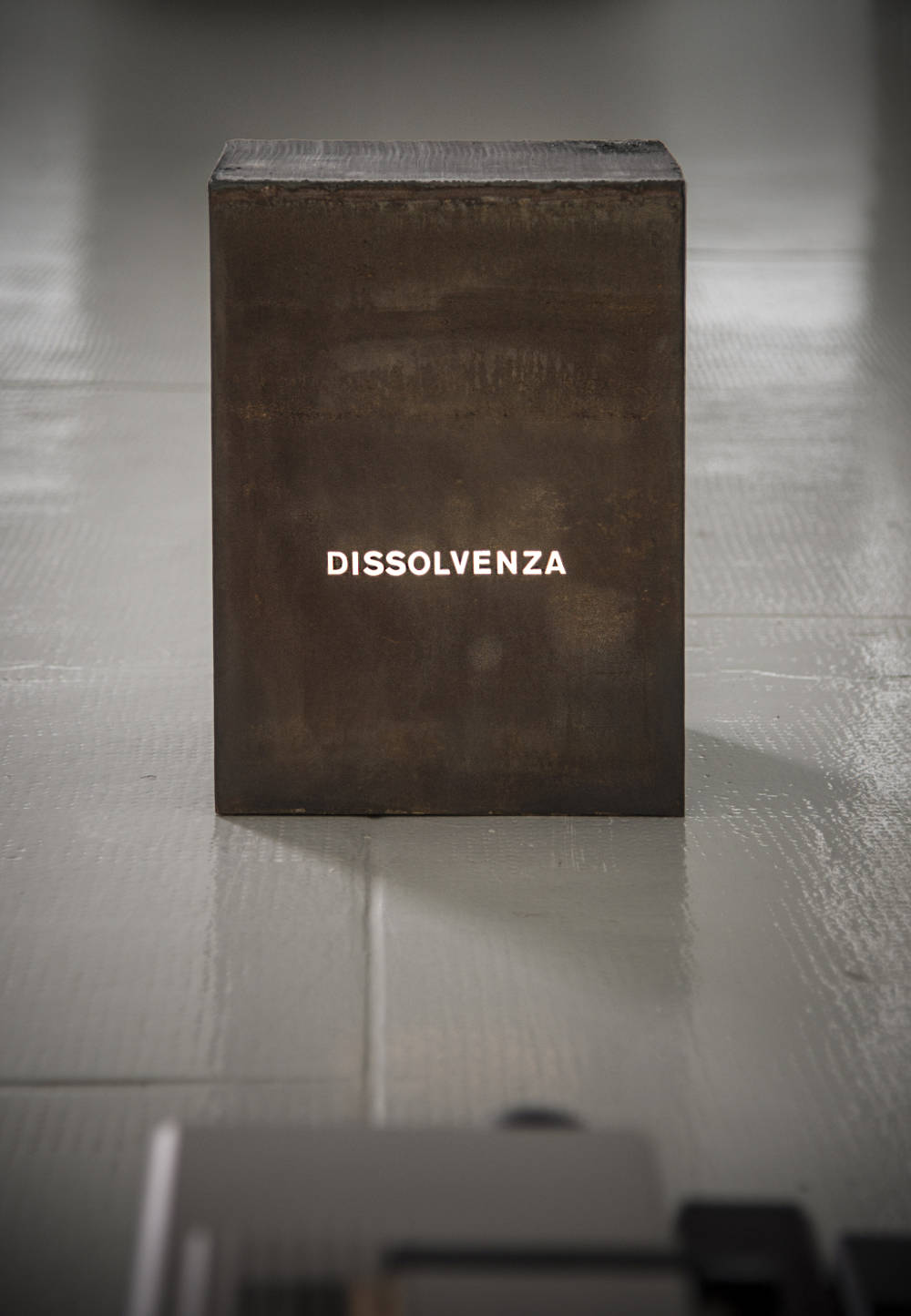 "Giovanni Anselmo, Dissolvenza, 1970. Iron, projector, slide with the word ""dissolvenza"" Cm 39 x 24 x 28"