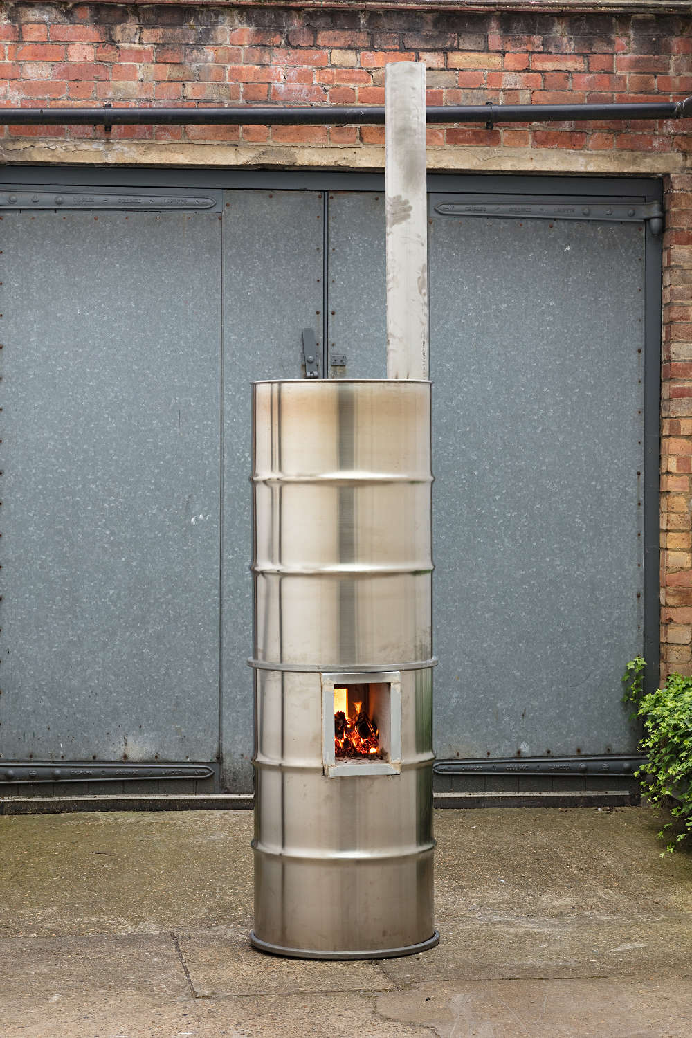 Oscar Tuazon, (FIRE) for Winona La Duke [Peter van den Berg, Antoine Rocca], 2018. Stainless steel, refractory brick, wood, fire 250 x 60 x 60 cm © Oscar Tuazon, courtesy Maureen Paley, London