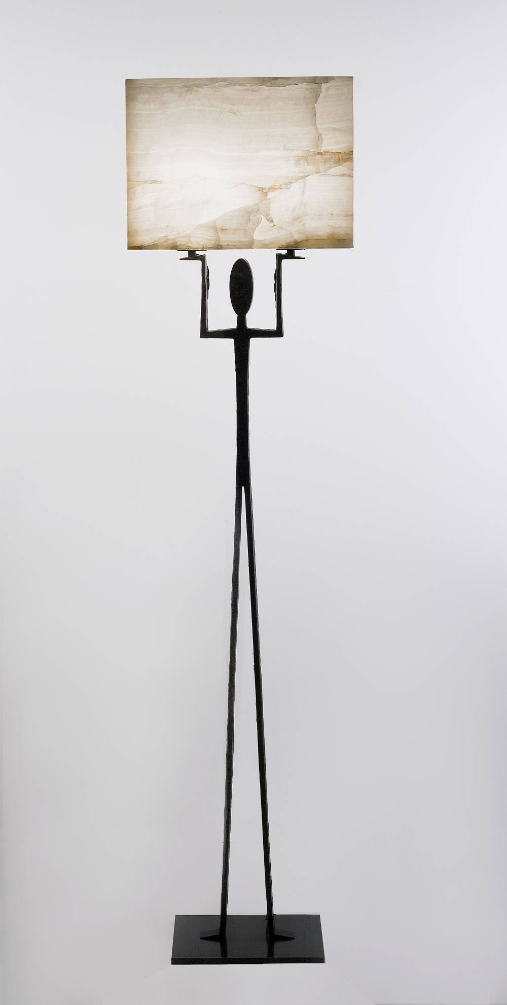 """Hercules, 2013. Limited Edition of 20 pieces + AP. Floor lamp with base formed by a burnished cast bronze stylised figure (silhouette) on a rectangular base holding a backlit hand-carved onyx block lamp share. Light source: 2 x 40W Clear E27. Height: 63.75"""" (162cm) - Width: 15.75"""" (40cm) - Depth: 10"""" (25cm). Weight: 29kg"""