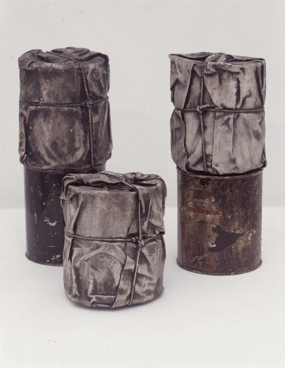 Christo, Packed Cans, 1958-59. Group of 5 cans (3 wrapped) lacquered canvas and twine 12.7 x 11.5 cm wrapped, 12 x 10.5 cm unwrapped © the Artist. Courtesy Annely Juda Fine Art, London