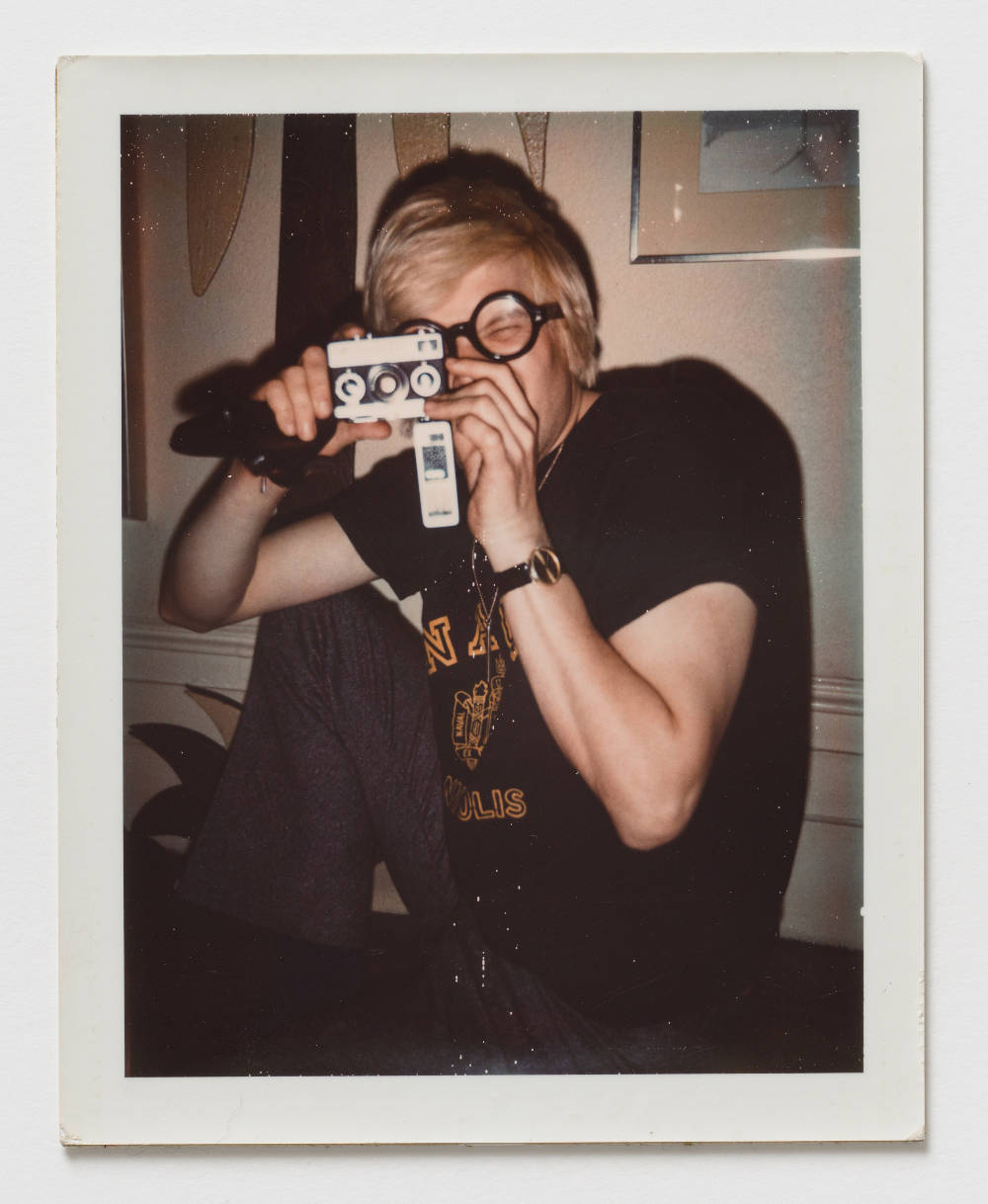 Andy Warhol, David Hockney, ca. 1972. Polaroid 10.7 x 8.5 cm / 4.2 x 3.4 in. [H x W] Inscribed verso lower centre in pencil FB05.00292; stamped verso lower left and lower right Authorized by the Andy Warhol Foundation for the Visual Arts, The Estate of Andy Warhol. © 2018 The Andy Warhol Foundation for the Visual Arts, Inc. / Licensed by DACS, London. Courtesy BASTIAN, London