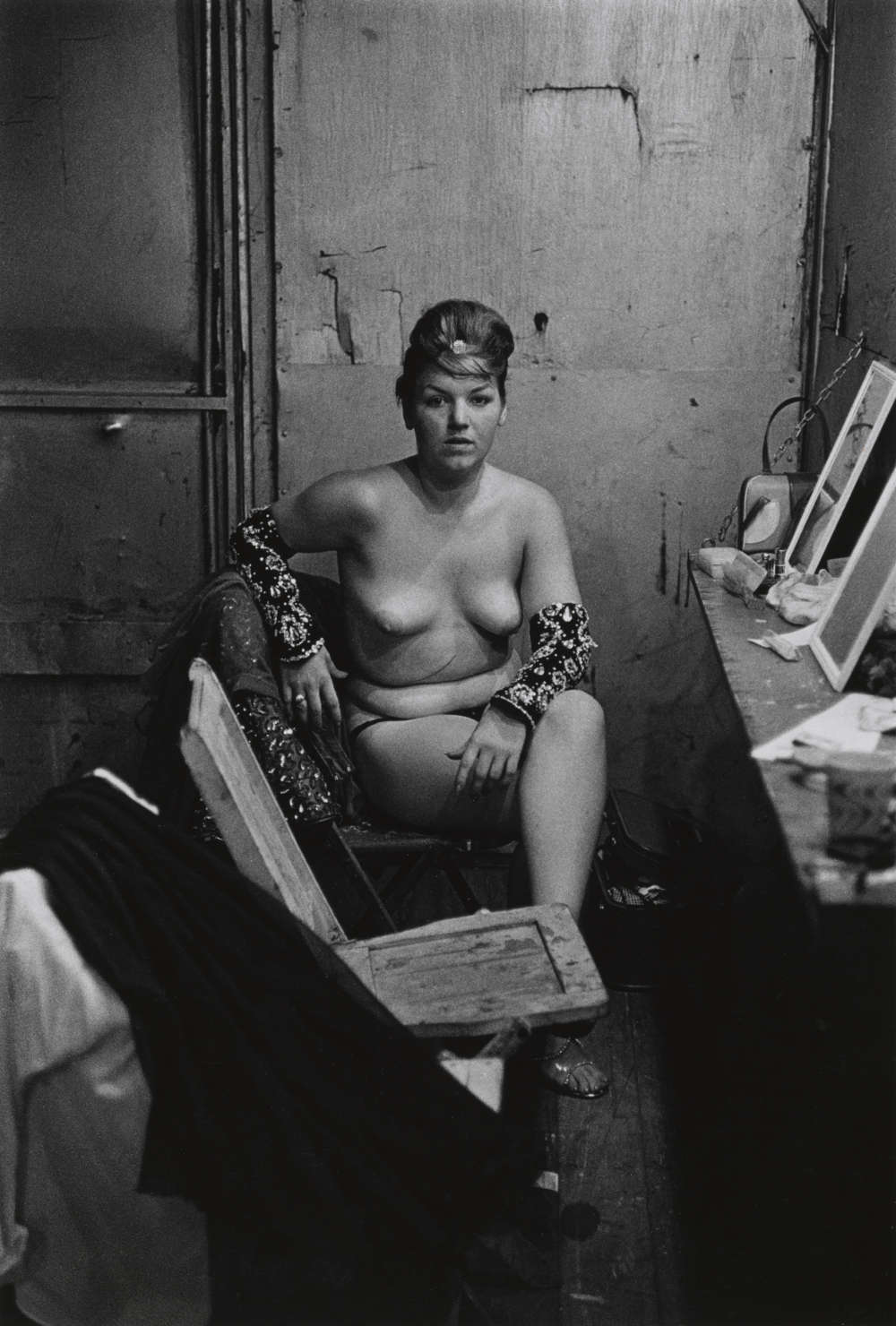 Stripper with bare breasts sitting in her dressing room, Atlantic City, N.J. 1961. 9 1/2 × 6 1/2 in. (24.1 × 16.5 cm) Purchase, Jade Lau Gift, 2015. Courtesy The Metropolitan Museum of Art, New York. Copyright © The Estate of Diane Arbus, LLC. All Rights Reserved