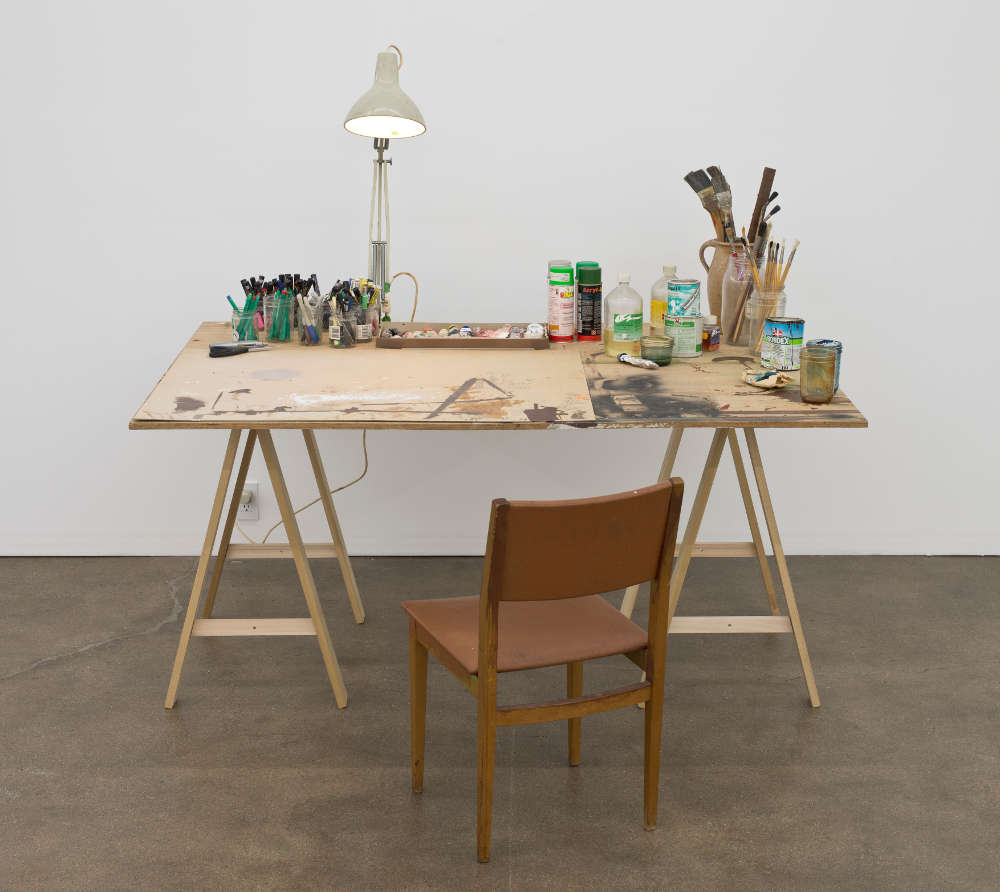 Dieter Roth / Björn Roth, Table Hegenheimerstrasse, 1980-2010. Acrylic paint, pencil, felt tip pen, marker, ball pen and collage (plastic adhesive tape, transparent plastic foil) on chipboard; 2 sawhorses, chair, lamp, ceramic jar, glass jars, brushes, markers, pens, scissors, utility knife, paint cans, spray paint can, paper towel, cardboard tray of oil color paint 167.6 x 164.5 x 121.9 cm / 66 x 64 3/4 x 48 in © Dieter Roth Estate. Courtesy the Estate and Hauser & Wirth. Photo: Brian Forrest