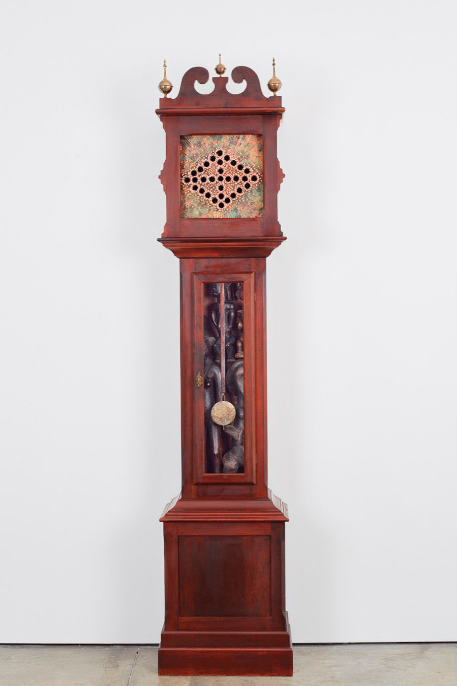 Nari Ward, Anchoring Escapement; Mahogany Ithaca, 2018. Grandfather clock case, copper sheet with patina, copper nails, and African copper nails, and African statues 218.4 x 50.8 x 30.5 cm (85.98 x 20 x 12.01 in) Courtesy the artist and Lehmann Maupin, New York, Hong Kong, and Courtesy the artist and Lehmann Maupin, New York, Hong Kong, and Seoul © Nari Ward. Photo: Matthew Hermann