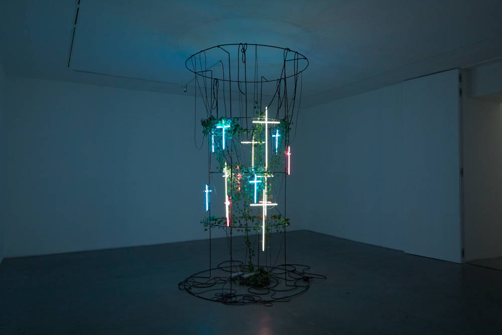 Bianca Bondi, Have you accepted Christ as your personal savior? I considered telling her we hung our gods from trees but thought better of it, 2019. Neons, steel structure, plants 320 x 180 cm (125.98 x 70.87 inches) Courtesy of the artist & VNH Gallery. Photo: Johanna Benaïnous