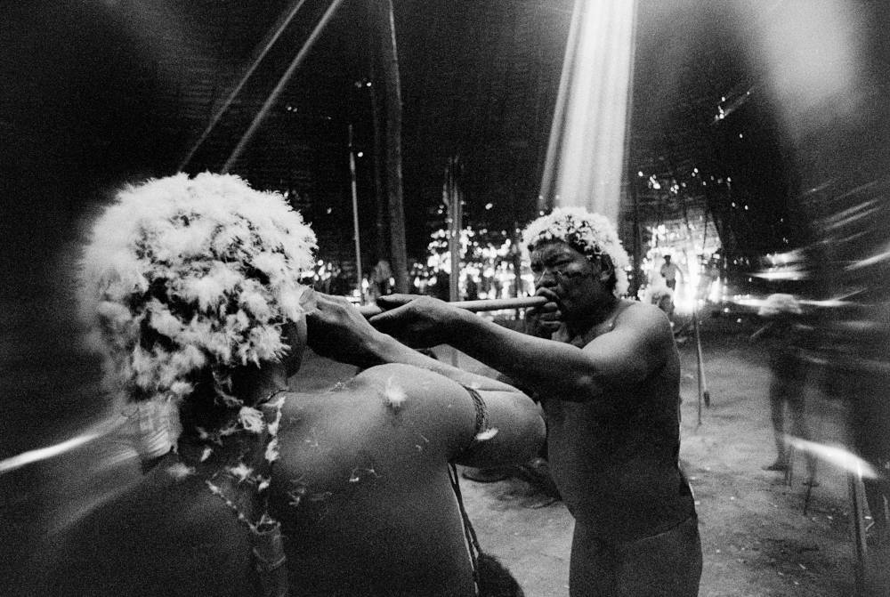 The shaman Tuxaua João blows on the hallucinogen yãkoana in the nostrils of a young man at the end of the reahu feast, Catrimani, Roraima, 1974. / Tomé Xaxanapi thëri inhales the hallucinogen yãkoana, Catrimani, Roraima, 1974