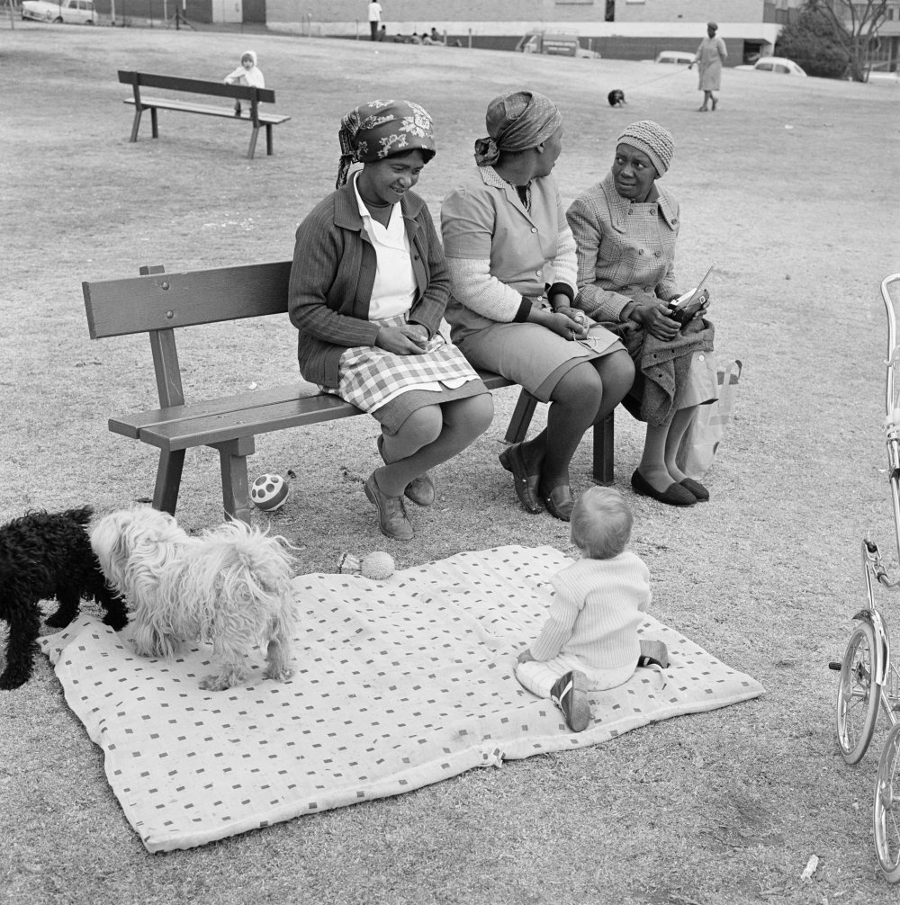 Baby with child-minders and dogs in the Alexandra Street Park, Hillbrow, 1972